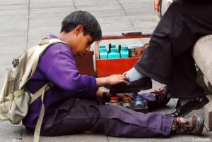 Niño trabajando en Quito limpiando botas