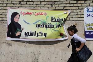 """Una niña pasa cerca de un cartel que dice """"la Ley Jaafari de estatus personal salva mis derechos y mi dignidad"""" / AP"""
