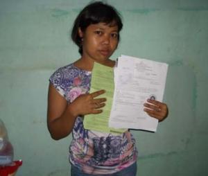 Una trabajadora doméstica indonesia sostiene el contrato engañoso por el que fue abusada en Hong Kong / Amnistía Internacional, Norma Kang Muico