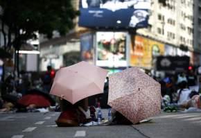 Dos manifestantes protestan sentados y protegidos por sus paraguas en el distrito Central de Hong Kong / DENNIS M. SABANGAN - EFE