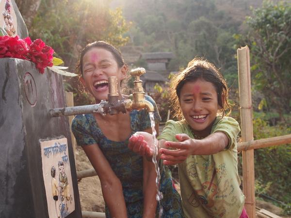 Las hijas de Nara Bahadur's contentas de ver agua saliendo del grifo. Tosramkhola, Sindhuli, Feb 2013 / Water Aid
