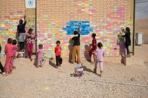 Un grupo de niños refugiados pinta un mural con la bandera europea en el campo de refugiados de Arbat (Kurdistán iraquí) / EUROPEAN COMISSION DG ECHO